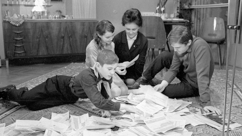 Жена космонавта Владимира Шаталова, Муза Андреевна (в центре), с детьми читают поздравления с успешным завершением полета космического корабля «Союз-4», 1969 год