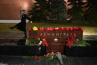 Люди приносят цветы и свечи на мемориал города Ленинграда на аллее городов-героев в Москве