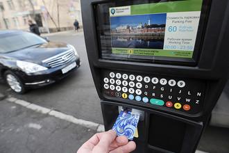 Прохожий производит оплату парковки в паркомате