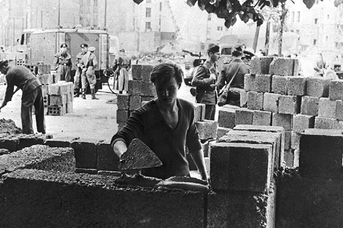 Рабочий закладывает первые камни Берлинской стены, 13 августа 1961 года