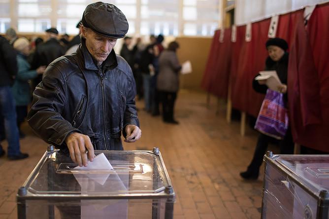 Луганск. Житель города во время голосования на выборах главы ЛНР и депутатов народного совета республики на избирательном участке