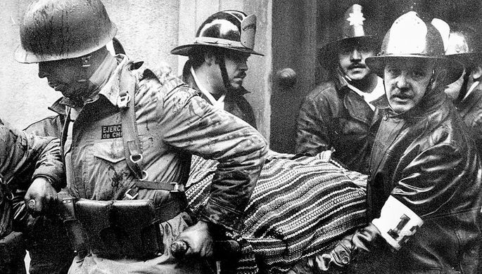 Военнослужащие и пожарные с телом президента Чили Сальвадор Альенде около разрушенного во время переворота дворца «Ла Монеда» в Сантьяго, 11 сентября 1973 года