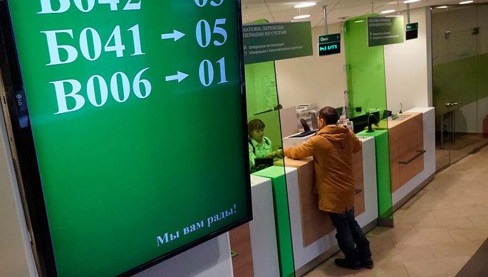 Сотрудница банка во время работы с клиентом в отделении Сбербанка РФ