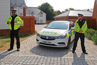 Сотрудники британской полиции в оцеплении около жилых домов после инцидента с отравлением в Эймсбери, 4 июля 2018 года