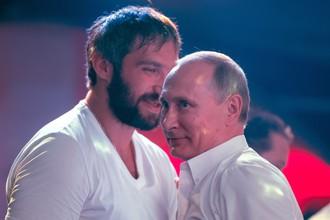 Президент России Владимир Путин (справа) и российский хоккеист Александр Овечкин во время посещения турнира по боевому самбо в Сочи