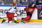 Сергей Плотников (слева) тянется заДжошуа Моррисси вполуфинале чемпионата мира похоккею Россия — Канада