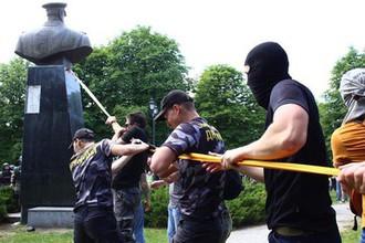 Представители националистических организаций с помощью троса пытаются повалить бюст маршала Георгия Жукова в Харькове возле Дворца спорта, 2 июня 2019 года