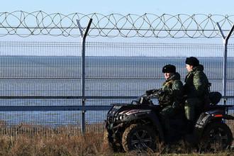 Российские пограничники у заграждения, возведенного в Крыму на границе с Украиной, 28 декабря 2018 года