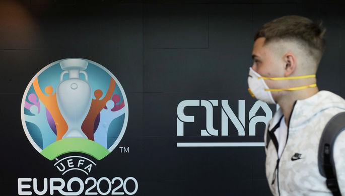 Человек в маске от коронавируса на фоне логотипа Евро-2020 по футболу