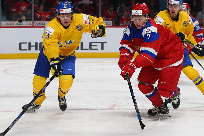 Игрок сборной Швеции Лукас Карлссон и игрок сборной России Кирилл Капризов (справа) в матче за 3-е место молодёжного чемпионата мира по хоккею между сборными командами России и Швеции