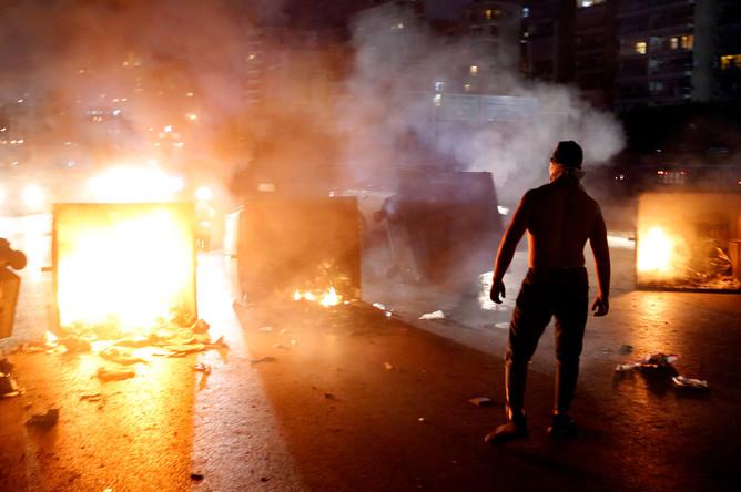 Сторонник премьер-министра Ливана Саада Харири с горящими мусорными баками на центральной улице Бейрута, 29 октября 2019 года