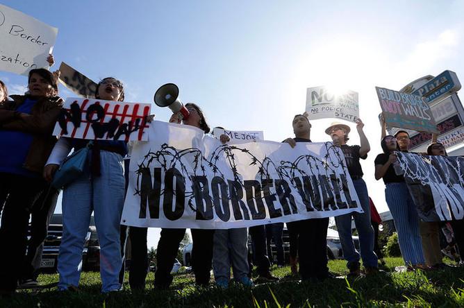 Люди, выступающие против воздвижения стены на границе США и Мексике, ожидают приезд президента США Дональда Трампа в Мак-Аллен