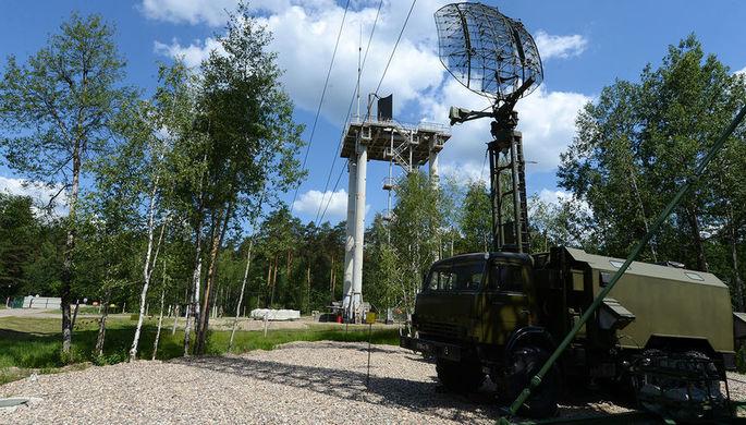 На позиции радиолокационной роты. На переднем плане – подвижная трехкоординатная радиолокационная станция дециметрового диапазона кругового обзора дежурного режима «Каста-2Е2» (39Н6). Предназначена для контроля воздушного пространства, определения координат и опознавания воздушных целей, в том числе на предельно малых высотах, их трассовых характеристик и выдачи их координат и параметров движения на системы управления ПВО.<br><br>На заднем плане – унифицированная многофункциональная вышка УМВ-30. Высота сооружения – 30 метров. Наверху – трехкоординатная радиолокационная станция дециметрового диапазона боевого режима 35Д6