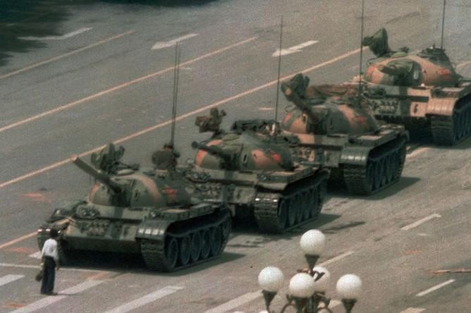 Мужчина стоит один, чтобы заблокировать линию танков, направляющихся на восток на бул. Канган в Пекине