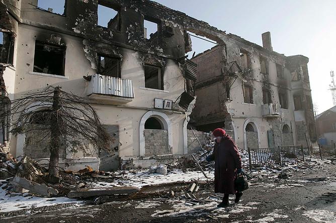 Женщина проходит мимо разрушенного здания в городе Углегорск под Донецком
