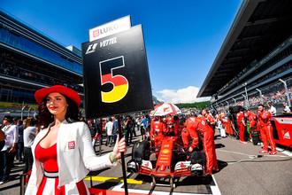 Девушка держит табличку с номером места гонщика команды «Феррари» Себатьяна Феттеля на трассе перед гонкой на российском этапе чемпионата мира по кольцевым автогонкам в классе «Формула-1»
