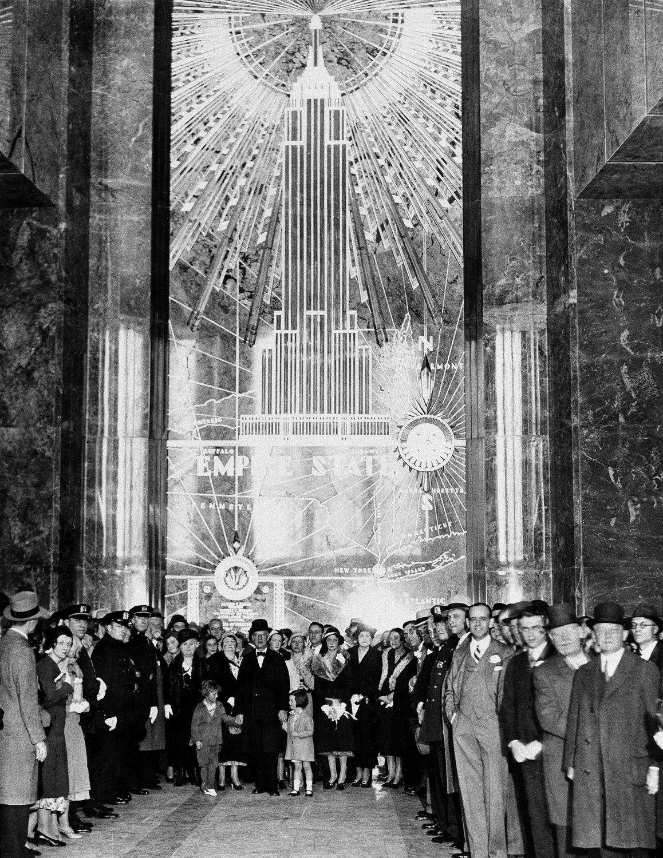 1 мая 1931 года состоялось торжественное открытие объекта. В тот день президент США Герберт Гувер включил освещение здания, нажав на кнопку в Вашингтоне. На месте событий праздничную ленточку перерезал губернатор штата Нью-Йорк Франклин Рузвельт. Это принесло ему удачу: через 1,5 года Рузвельт победил Гувера на президентских выборах, и верхушку Эмпайр-стейт-билдинг подсветили в честь его триумфа. На фото: экс-губернатор Альфред Смит (в центре) и другие гости на церемонии открытия Эмпайр-Стейт-билдинг, 1 мая 1931 года