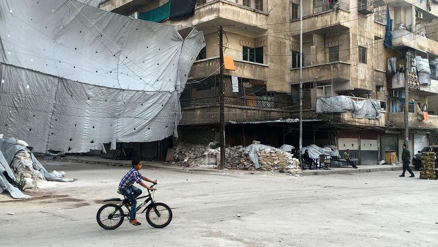 Ребенок у КПП Бустан аль-Каср на месте, где начинается коридор для боевиков, принявших решение...