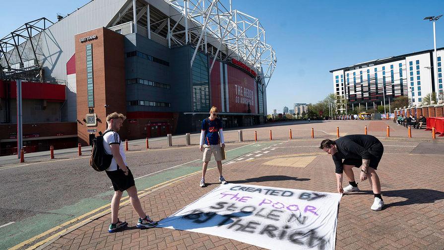 Болельщики размещают баннер у стадиона в Манчестере, 19 апреля 2021 года