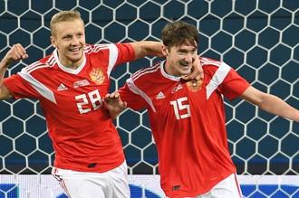 Игроки сборной России Игорь Смольников и Алексей Миранчук (справа) радуются забитому мячу в товарищеском матче между сборными командами России и Испании.