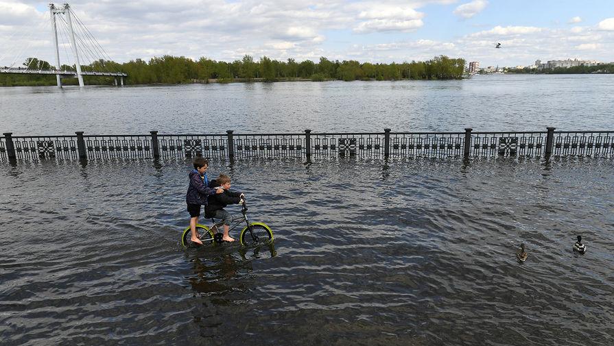 Дети катаются на велосипеде по затопленной набережной Енисея в центре Красноярска, 2021 год