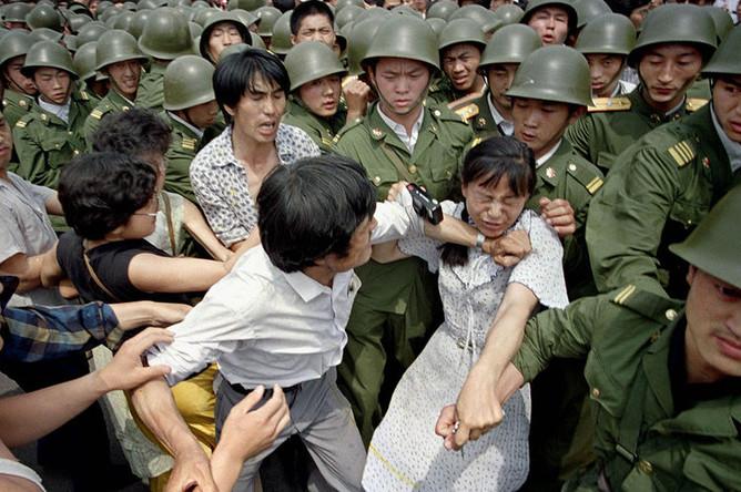 Молодая женщина между гражданскими лицами и китайскими солдатами, 3 июня 1989 года