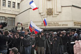 Журналисты работают у здания Верховного совета Крыма в Симферополе, где проходит митинг, 25 февраля 2014 года