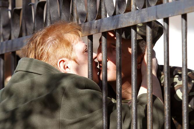Женщина целует украинского военнослужащего на территории военного объекта в 80 километрах юго-западнее Симферополя