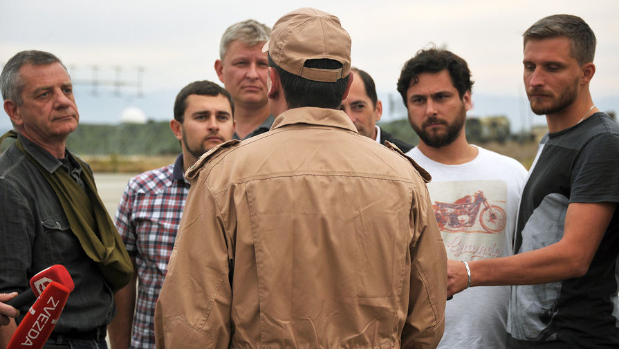 Спасенный летчик Су-24Военно-космических сил России капитан Константин Мурахтин (в центре) отвечает навопросы журналистов наавиабазе Хмеймим всирийской Латакии