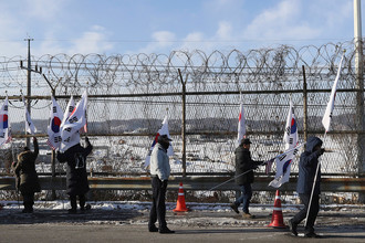 Жители Южной Кореи стоят с флагами у границы с Северной Кореей, 25 января 2018 года