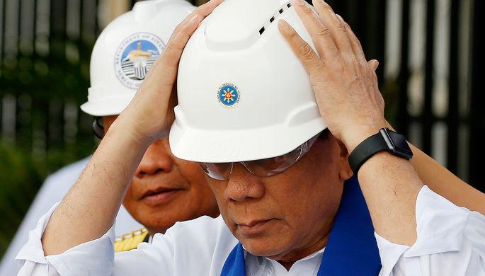 Президент Филиппин Родриго Дутерте в защитных очках и каске перед торжественным уничтожением...