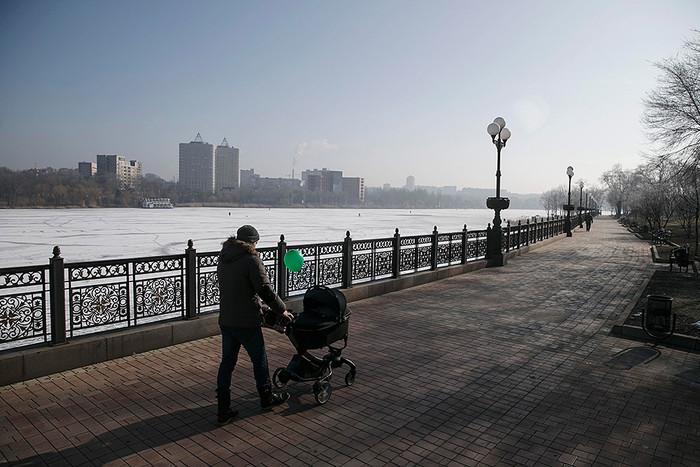 Мужчина гуляет с ребенком у замерзшей реки в Донецке