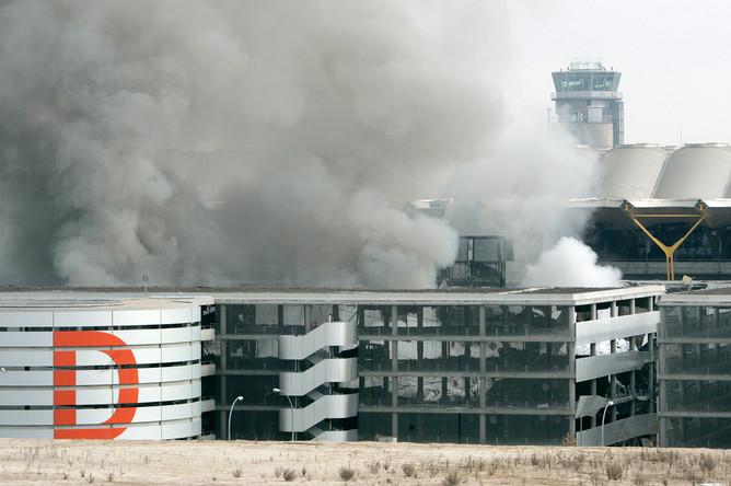 Дым поднимается над одной из парковок в аэропорту Мадрида Барахас после взрыва автомобиля, устроенного предположительно боевиками ЭТА, 30 декабря 2006 года