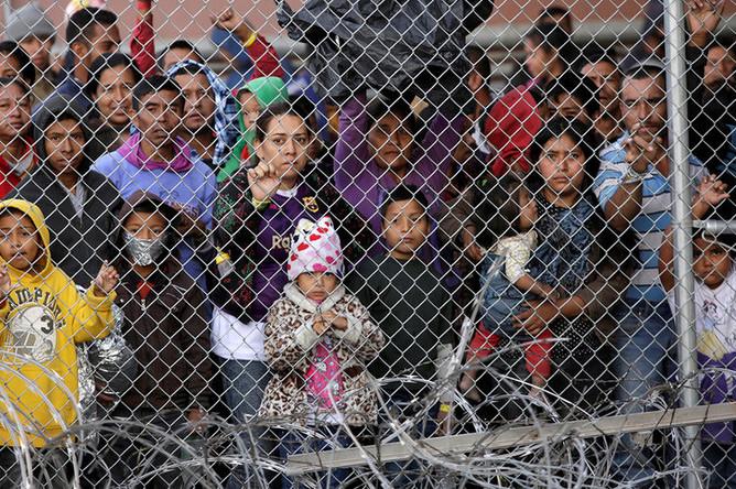 Мигранты у ограждения после нелегального перехода граница между Мексикой и США в Эль-Пасо, штат Техас, март 2019 года