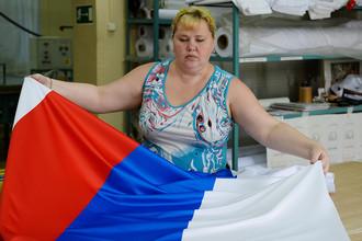 Сотрудница предприятия по производству флагов в Новосибирске во время работы, 2013 год