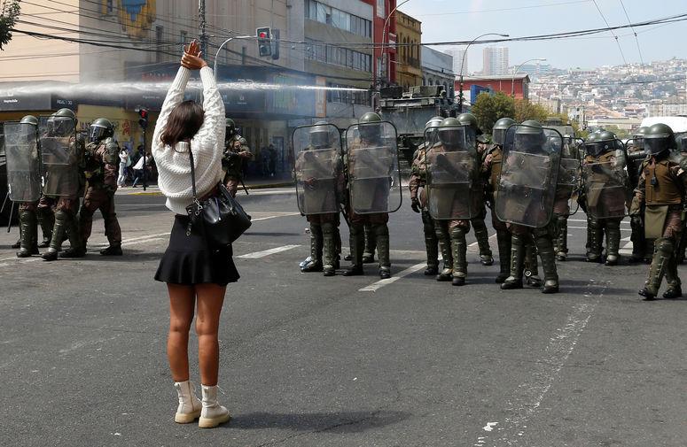Полицейские и участница акции протеста в честь Международного женского дня в Вальпараисо, Чили, 8 марта 2021 года