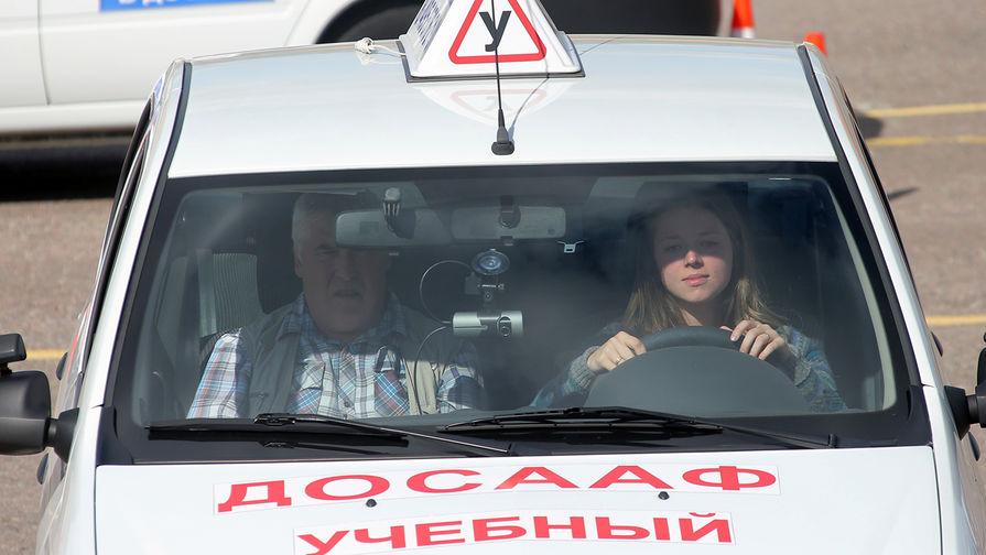 Девушка с инструктором во время практических занятий в автошколе