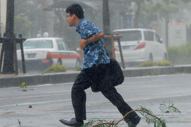 Идущего по пешеходному переходу мужчину сносит сильным ветром, вызванным тайфуном «Неогури», на южном японском острове Окинава