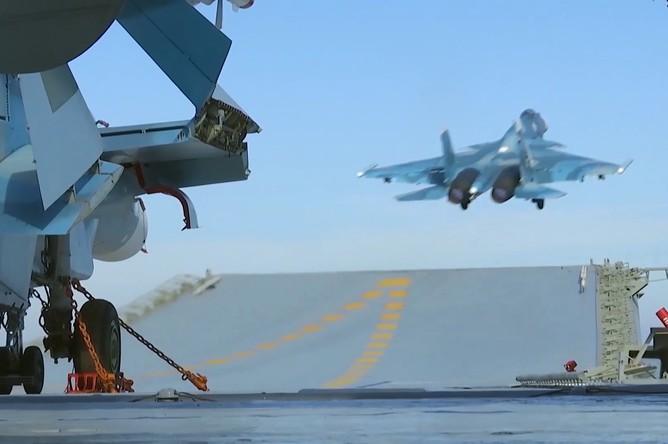Истребитель Су-33 производит взлет с палубы тяжёлого авианесущего крейсера «Адмирал Флота Советского Союза Кузнецов» у берегов Сирии в Средиземном море. Крейсер «Адмирал Кузнецов» и СКР «Адмирал Григорович» впервые задействованы в операции в Сирии