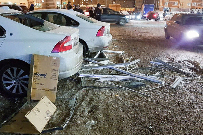 Поврежденные автомобили около жилого дома в подмосковной Балашихе, где горела одна из квартир, 24 января 2019 года