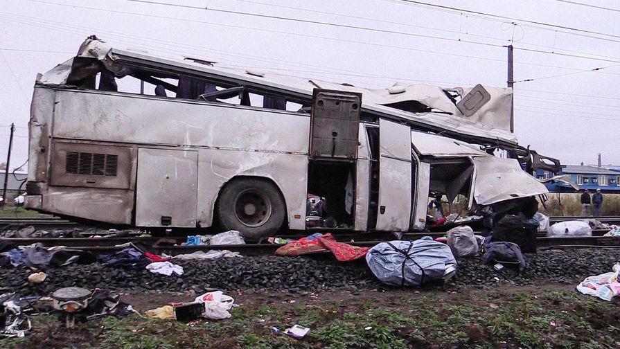Последствия столкновения пассажирского автобуса с поездом на железнодорожном переезде во...
