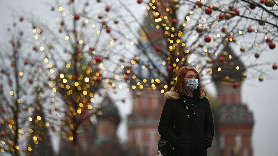 Девушка в защитной маске на улице в Москве, декабрь 2020 года