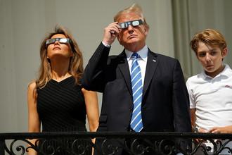 Президент США Дональд Трамп со своей женой Меланьей Трамп и сыном Бэрроном наблюдают за солнечным затмением с крыльца Белого дома, 21 августа 2017 года