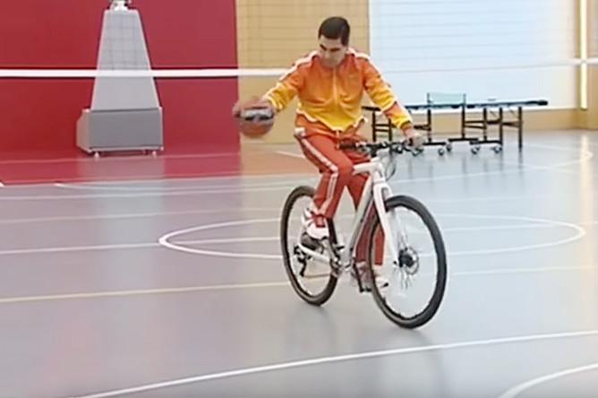 Президент Туркменистана Гурбангулы Бердымухамедов с баскетбольным мячом на велосипеде во время тренировки для глав силовых министерств, ноябрь 2017 года