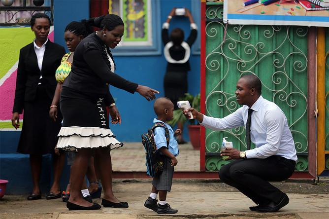 Сотрудник школы измеряет температуру учеников при помощи инфракрасного термометра, Лагос