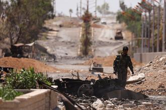 Ополченец «Демократических сил Сирии» (SDF) на улице отбитого у террористов сирийского города Табка, 12 мая 2017 года