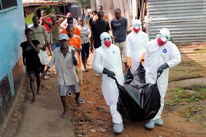 Бригада врачей выносит тело 29-летнего местного жителя, погибшего от вируса Эбола в Монровии