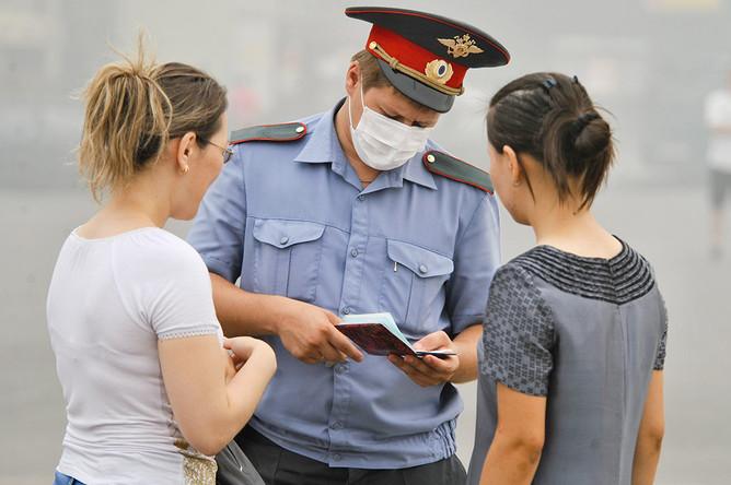 Сотрудник милиции в медицинской маске во время проверки документов на одной из улиц столицы, август 2010 года
