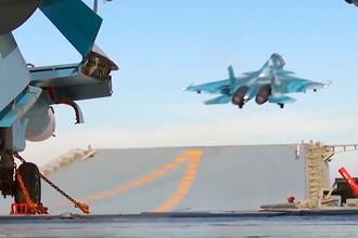 Корабельный истребитель Су-33 ВКС РФ во время взлета с палубы тяжелого авианесущего крейсера «Адмирал Кузнецов»