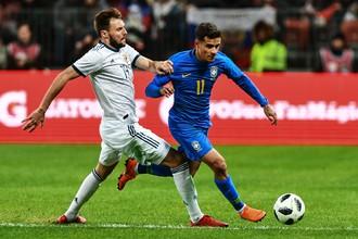 Защитник сборной России Владимир Гранат пытается остановить бразильского полузащитника Филиппе Коутиньо